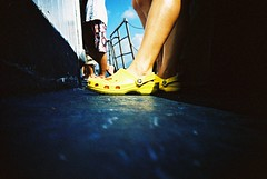 yellow crocodile on the deck (* andrew) Tags: blue color film feet yellow shoe lomo lca crossprocessed xprocess leg ct slide vessel deck footwear 100 cayman agfa crocs 32mm precisa ratview