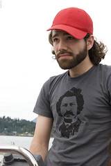 Steph Steers (Lindsay Beyerstein) Tags: red man hat vancouver beard boat cap sail helm threequarter