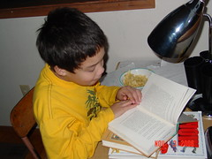 Studying (gehirin) Tags: yellow reading child eating snacking studytable