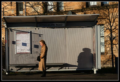 J060208L ~ Life (moi_images) Tags: road woman sun bus standing waiting glasgow shaddow stop shelter springburn