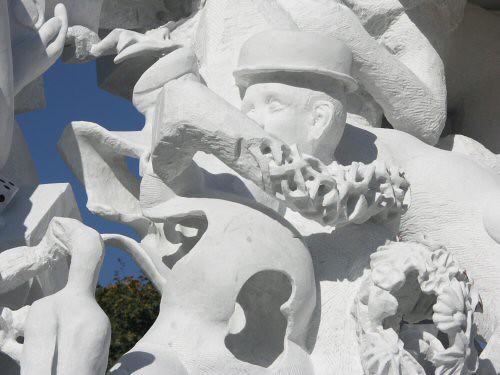 Sculpture monumentale en marbre de Carrare dont l'un des personnages est une femme enceinte. Son torse est ouvert sur le côté avec des courbes sinueuses et laisse voir l'intérieur qui est creux et son visage est figuré par un masque partiel – Sandrine Vallée