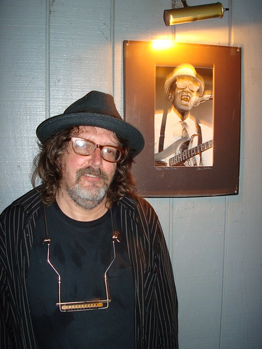 A picture of Peter Case in front of Sleepy John Estes at the Rhythm Room in Phoenix Arizona