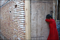 red dress - Kashgar China (Maciej Dakowicz) Tags: china travel red brick tourism girl wall children asia child dress xinjiang historical kashgar cry oldtown kashgaroldtown