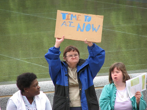 A woman holds up a sign reading Time to act... NOW!