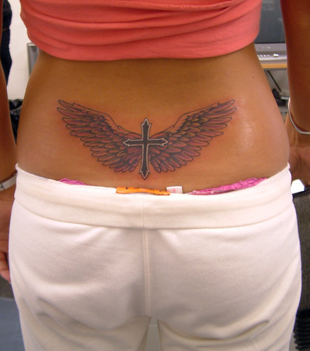 Lower back tattoo of a religions cross with wings.
