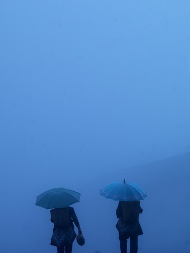 Two women with umbrellas in the fog and rain in Yuanyang, Yunnan, China by Eric Lafforgue