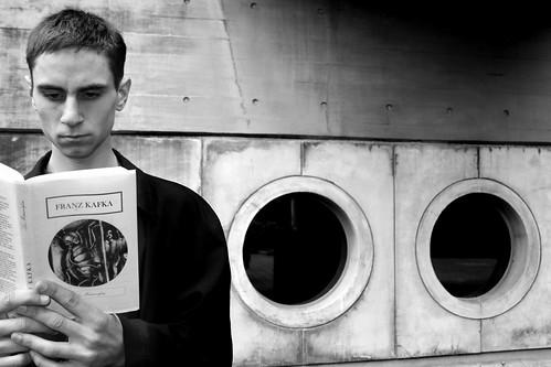 A boy reading book called The Metamorphosis by Franz Kafka.
