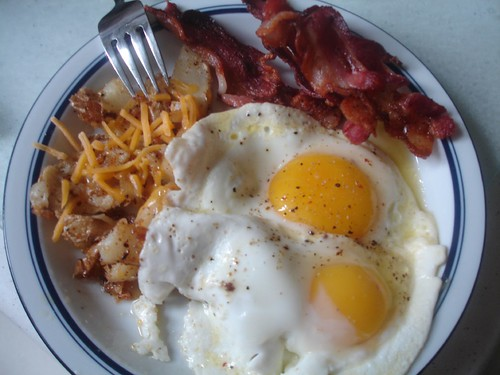 Two eggs sunny side up, bacon, and home fries with cheddar cheese