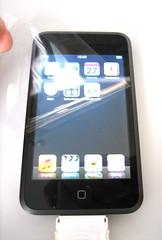 De folie die op het scherm zit kun je gebruiken om de zilverkleurige achterkant van de iPod Touch te beschermen tegen krassen.