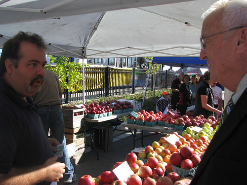 USDA Under Secretary Kevin Concannon talks with Kevin Tuckey from Tuckey's Mountain Grown Farm, who was selling fresh apples to shoppers at the Crossroads Farmers' Market in Tacoma Park, Maryland, Wednesday October 13.