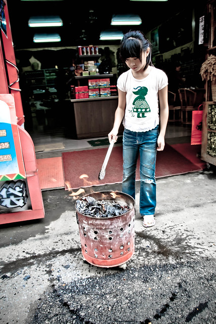 Girl tends a fire on WenHua St., near Sun Moon Lake, Taiwan