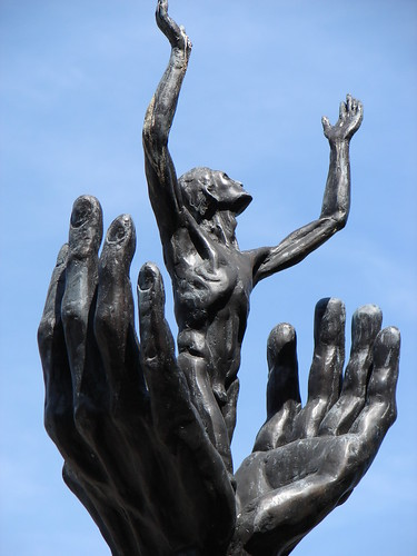Erupting from the structure of open hands (sculpture outside Creighton University)