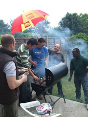 blokes by a barbecue in the rain under an umbrella