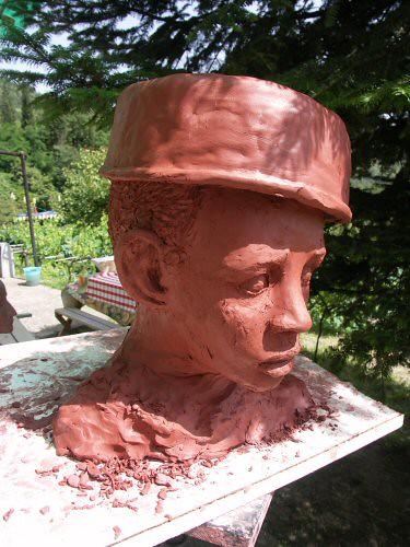 Sculpture en terre figurative vue de ¾ représentant la tête d'un enfant africain dont les cheveux sont recouverts d'un récipient renversé – Sandrine Vallée