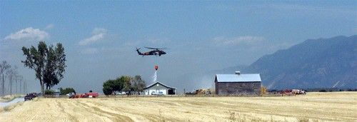 Helicopter dumping water on grass fire