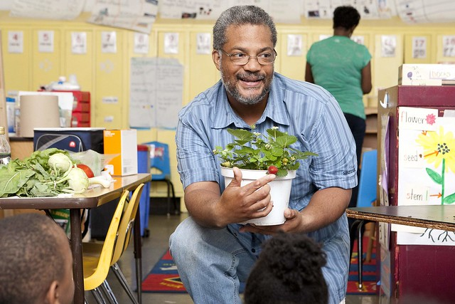 Carl Rollins with Common Good City Farm shows a strawberry plant to a group of pre-K students at Simon Elementary School.