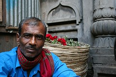 flower seller | Kolkata (arnabchat) Tags: blue portrait india flower look canon dof market favs kolkata bengal calcutta 400d arnabchat arnabchatterjee