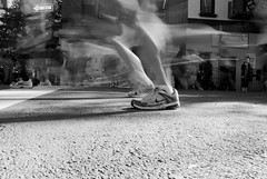 swoosh. (Vitaliy P.) Tags: street new york city nyc light shadow people bw sun white motion black monochrome brooklyn speed concrete bedford frozen movement nikon exposure slow angle natural muscle marathon low leg ground run nike shutter williamsburg sneaker runners gothamist avenue ing 2010 marathoners d80 18135mm vitaliyp gettysubmitted 2010nycmarathon