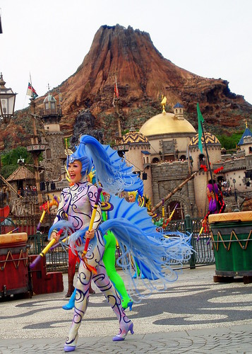 The dancers on shore use their bright colored costumes to attrack attention against the dark background.  Here we have a truly stunning photo of one of the beautifully dressed cast members performing against the parks icon volcano, Mt. Promethus.