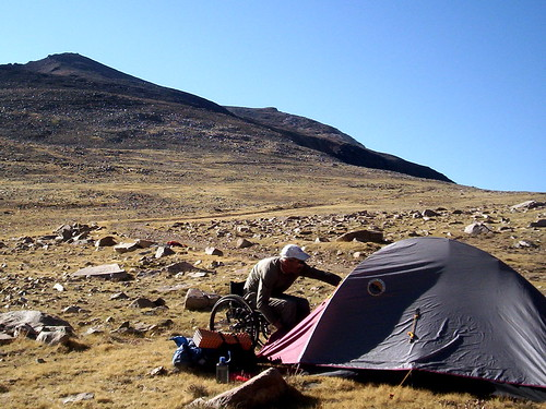 A wheelchair in a rocky, grassy landscape on a mountain. He is leaning forward to unzip a tent and camping equipment is stacked next to the tent's entry.