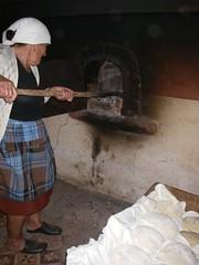 A avó a pôr os pães no forno