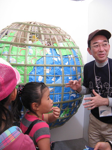 photo of a man with a globe talking to children
