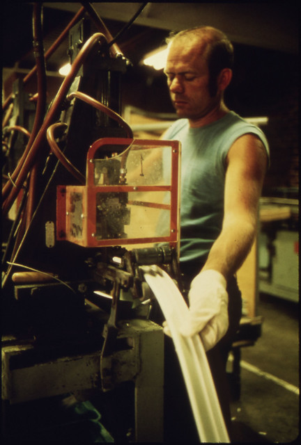 Employee of the BF Goodrich Co Working on a Machine That Makes Molding for Magnetic Door Seals for Various Brands of Refrigerators by The US National Archives