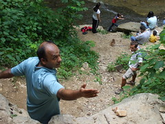 Hikers climbing down and children playing in the creek