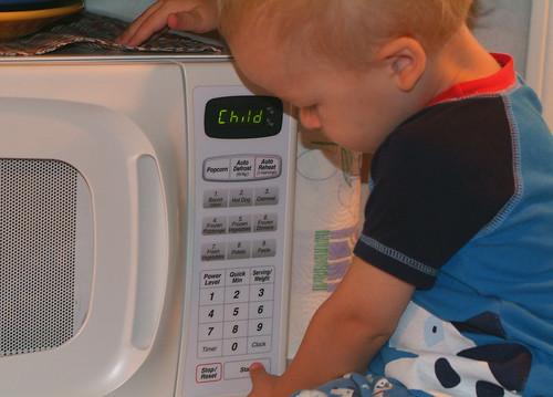 Imagen de un niño frente a los botones de un aparato microondas