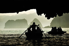 Under the Cave Tunnel of the Rocky Limestone Island ( DocBudie) Tags: silhouette boat tourists vietnam cave halongbay stockphoto floatingvillage traditionalboat rowingboat stockimage northernvietnam vietnamtourismdestination bestplacetovisitvietnam foaltingfishingvillage quangningh vietnamphotostock