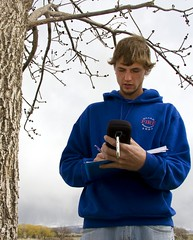 student recording in a field journal for a tree survey