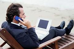 Werkverslaafd: laptop en mobieltje mee naar het strand