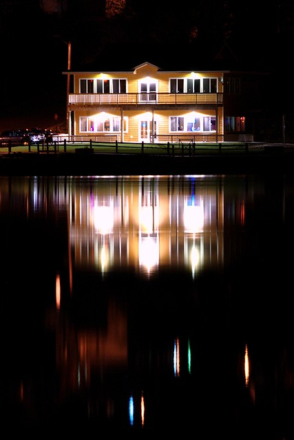 A house reflected in water at night.