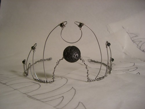 Completed tiara, formed by bending stainless steel wire and wiring glass and lava beads to it.