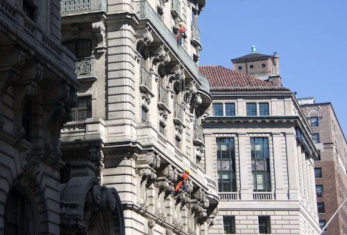 Men climbing the Ansonia Hotel