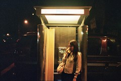 Kim in phonebooth with plank. (rollergirl PRG) Tags: newyorkcity film night 35mm phonebooth voigtlander rangefinder bessar2