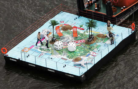 Giant monopoly game pulled by a barge