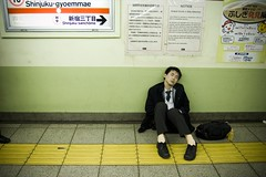 Exhausted man at Japanese train station by Flickr user a_malchik