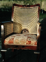 Upholstered chair with a cane 'sunset' back and caned arms