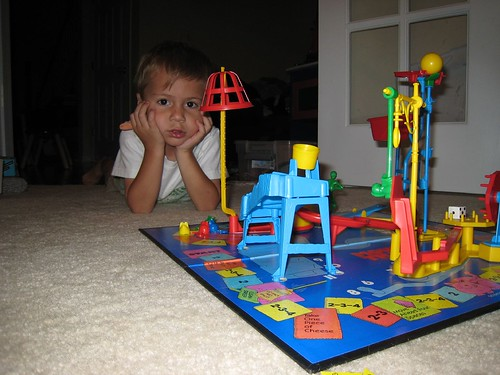 A young boy playing the Mouse Trap game, set up on the floor