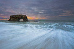 Natural Bridges sunrise (Andy Kennelly) Tags: california road santa trip motion wet rock clouds sunrise sand long exposure day waves arch natural pacific cloudy bridges wave formation cruz