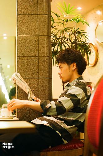 カフェで新聞を読む男性