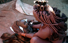 Himba child looking into her mother's eyes - Namibia (kryyslee) Tags: world pictures voyage africa trip travel red woman color travelling colors look canon hair photography eos photo foto tour child looking image photos pics couleurs african picture culture images tribal du adventure safari round afrika around tribe christophe monde ethnic backpacker amateur pict namibia autour couleur tribo indigenous himba afrique ethnology tribu aroundtheworld aventure namibie tourdumonde 50d tribus ethnie 400d himbas eos400d kryyslee christophepaquignon paquignon