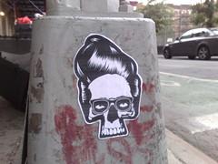 pompadour (lia) Tags: cameraphone nyc skull graffiti sticker lowereastside pompadour n95 nerdglasses