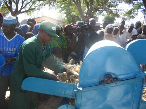 Technician operating maize threshing machine in a village