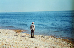 (Yellow Bear) Tags: blue sea portrait copyright man book brighton alone looking hove shingle pebbles lonely allrightsreserved lookingouttosea clairegriffiths brightonflickr2009bookpick