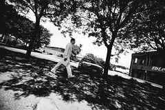 _MG_4813 (k.a. gilbert) Tags: trees shadow bw white man walking driveby fullframe 16mm 116 fromcar fromvehicle whiledriving tokina1116mmf28