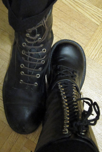 closeup of booted feet-- one combat boot, one knee-high goth/industrial boot