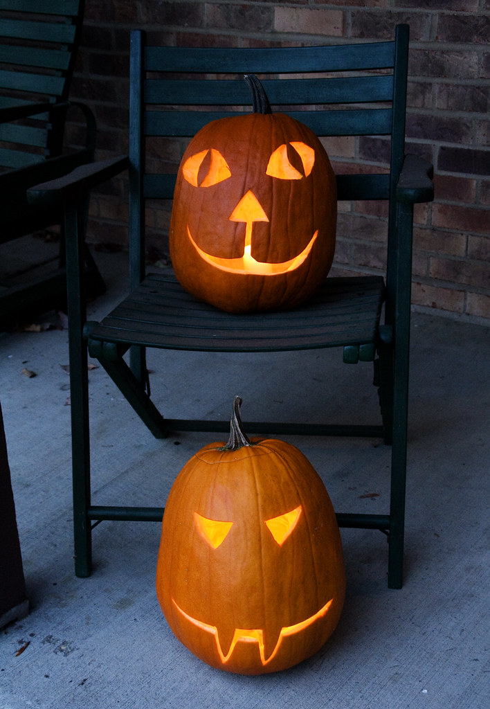 Halloween pumpkins on the front porch.  Mine is the one on the chair (happy cat pumpkin) and John's is in front of the chair (scary monster pumpkin)