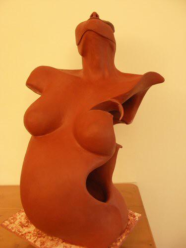 Sculpture en terre représentant le torse d'une femme enceinte vue de 3/4  dont un côté est ouvert et laisse voir l'intérieur qui est creux. Le visage est figuré par un masque partiel – Sandrine Vallée